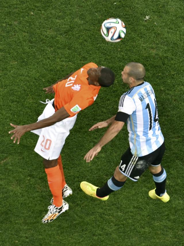 Georginio Wijnaldum of the Netherlands and Argentina's Javier Mascherano jump for a high ball during their 2014 World Cup semi-finals at the Corinthians arena in Sao Paulo July 9, 2014. REUTERS/Francois Xavier Marit/Pool (BRAZIL - Tags: SOCCER SPORT WORLD CUP)