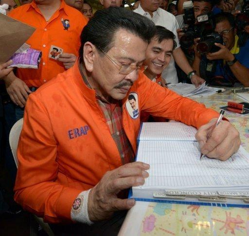 Former Philippine president Joseph Estrada signs documents at the Commission on Elections in Manila
