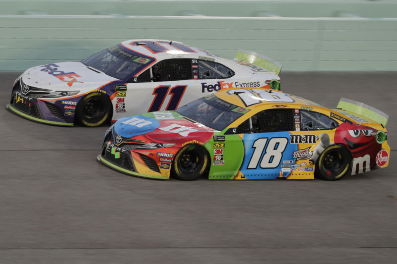Kyle Busch (18) and Denny Hamlin (11) are seen during the NASCAR Cup Series auto racing season championship race at Homestead-Miami Speedway in Homestead, Fla., Sunday, Nov. 17, 2019. Busch won the NASCAR Cup Series auto racing season championship.(AP Photo/Luis M. Alvarez)