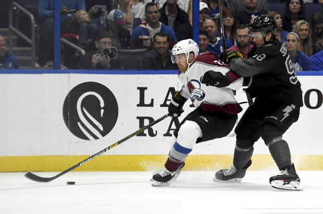 Colorado Avalanche center Colin Wilson (22) and Tampa Bay Lightning defenseman Mikhail Sergachev (98) battle for the puck during the first period of an NHL hockey game Saturday, Oct. 19, 2019, in Tampa, Fla. (AP Photo/Jason Behnken)