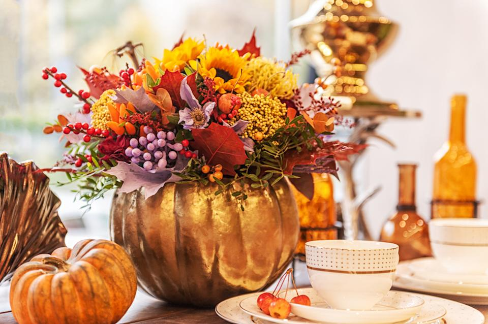 autumn flower composition in a pumpkin vase on a table decorated with pumpkins
