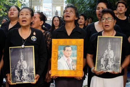 People hold portraits of Thailand's late King Bhumibol Adulyadej as they sing a national anthem at the Siriraj hospital in Bangkok, Thailand, October 14, 2016. REUTERS/Chaiwat Subprasom