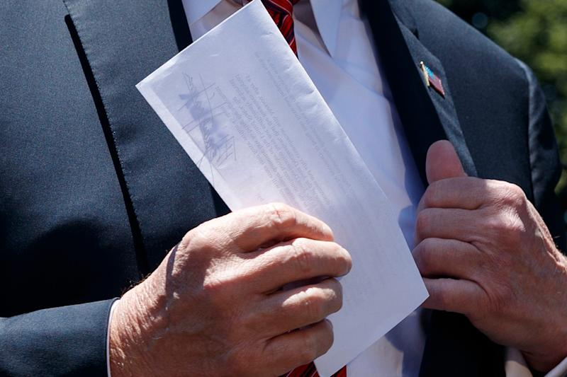 President Donald Trump holds a letter as he speaks to reporters before departing for a trip to Iowa, on the South Lawn of White House, Tuesday, June 11, 2019, in Washington. (AP Photo/Evan Vucci) ORG XMIT: DCEV318