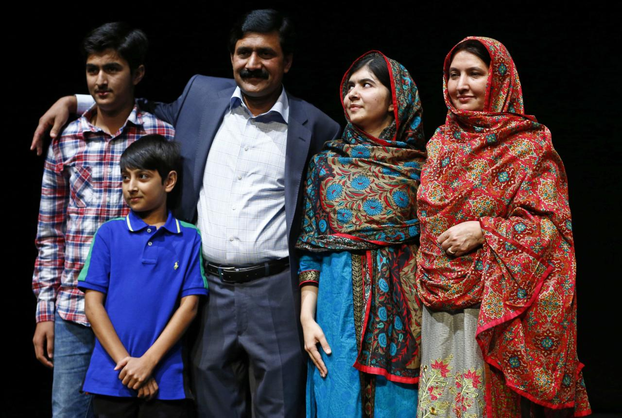 Pakistani schoolgirl Malala Yousafzai (2nd R), the joint winner of the Nobel Peace Prize, stands with her father Ziauddin (C), mother Torpekai (R), and brothers Atal (2nd L) and Khushal, after speaking at Birmingham library in Birmingham, central England October 10, 2014. Pakistani teenager Yousafzai, who was shot in the head by the Taliban in 2012 for advocating girls' right to education, and Indian campaigner against child trafficking and labour Kailash Satyarthi won the 2014 Nobel Peace Prize on Friday.  REUTERS/Darren Staples (BRITAIN - Tags: POLITICS SOCIETY EDUCATION TPX IMAGES OF THE DAY)
