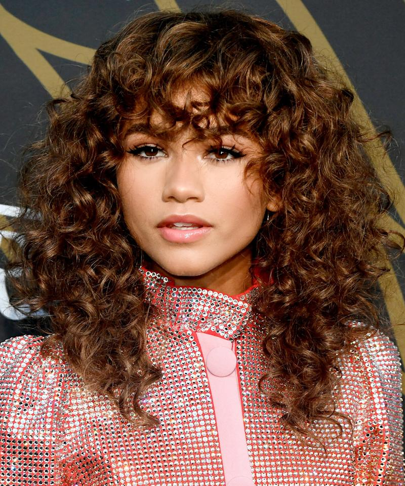 "<p>Zendaya's pro Larry Sims may have been inspired by Jennifer Beal in the '80s classic <em>Flashdance </em>when creating the star's look for the <em>Variety</em><em> </em>Young Hollywood Party, but there's nothing retro about this curly shag. When you're at the salon, Sims says to ask your stylist for a ""uniformed layered haircut with the front fringe as the guideline.""</p> <p>Zendaya's shag works for a number of hair textures from wavy to tightly coiled, but Sims says to keep in mind that ""the tighter the curl, the bigger the cut's shape"". When styling a cut like Zendaya's, he recommends running a curl-enhancing mousse such as Smooth 'N Shine Curled Up Mousse ($3; <a href=""http://goto.target.com/c/249354/81938/2092?subId1=IS%2CFallHaircuts-5%2Ckanej%2C%2CIMA%2C3030701%2C201708%2CI&u=https%3A%2F%2Fwww.target.com%2Fp%2Fsmooth-n-shine-curled-up-curl-activating-mousse-with-jojoba-oil-9-oz%2F-%2FA-13946653"" target=""_blank"">target.com</a>) through damp hair and letting it almost completely air dry because ""you get the best defined curls with a no-touch air dry"". Finish drying with a diffuser for extra volume, and use a curling wand on curls as needed. Lightly spritz your style with a shine spray like Smooth 'N Shine Instant Repair Spray-On Hair Polisher ($5; <a href=""http://www.anrdoezrs.net/links/7799179/type/dlg/sid/IS%2CFallHaircuts-5%2Ckanej%2C%2CIMA%2C3030701%2C201708%2CI/https://www.walgreens.com/store/c/smooth-n-shine-instant-repair-spray-on-hair-polisher/ID=prod5143331-product"" target=""_blank"">walgreens.com</a>) to separate curls. </p>"