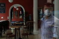 A man wearing a protective mask is reflected on the window of a closed vermouth bar, amid the coronavirus disease (COVID-19) outbreak, in Madrid