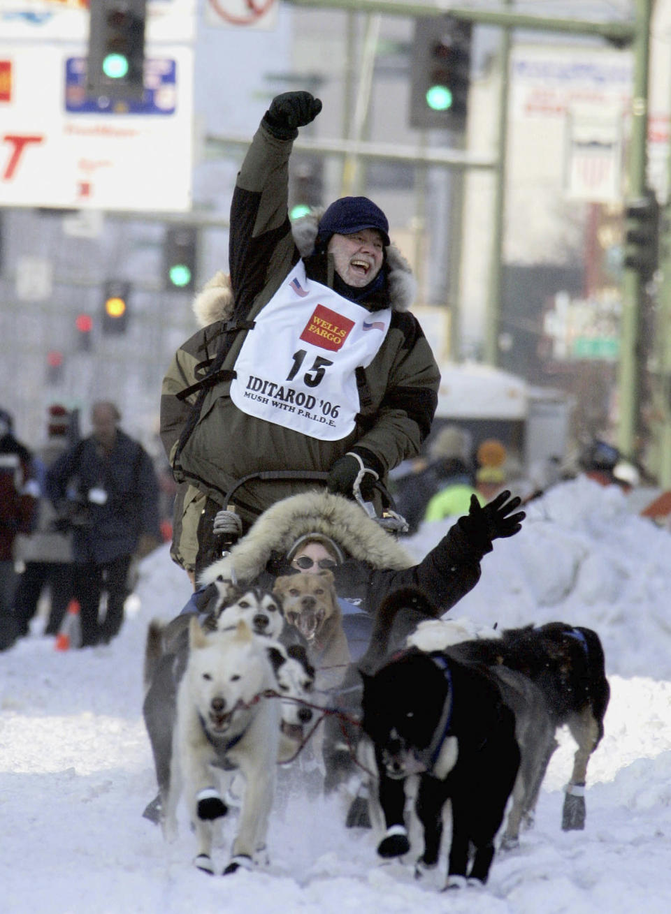 FILE - Author Gary Paulsen cheers he drives his dog team down Fourth Avenue with Carole Markell in the sled, during the ceremonial start of the Iditarod Trail Sled Dog Race on March 4, 2006, in Anchorage, Alaska. Paulsen died Wednesday, Oct. 13, 2021 at age 82. (AP Photo/Al Grillo, File)