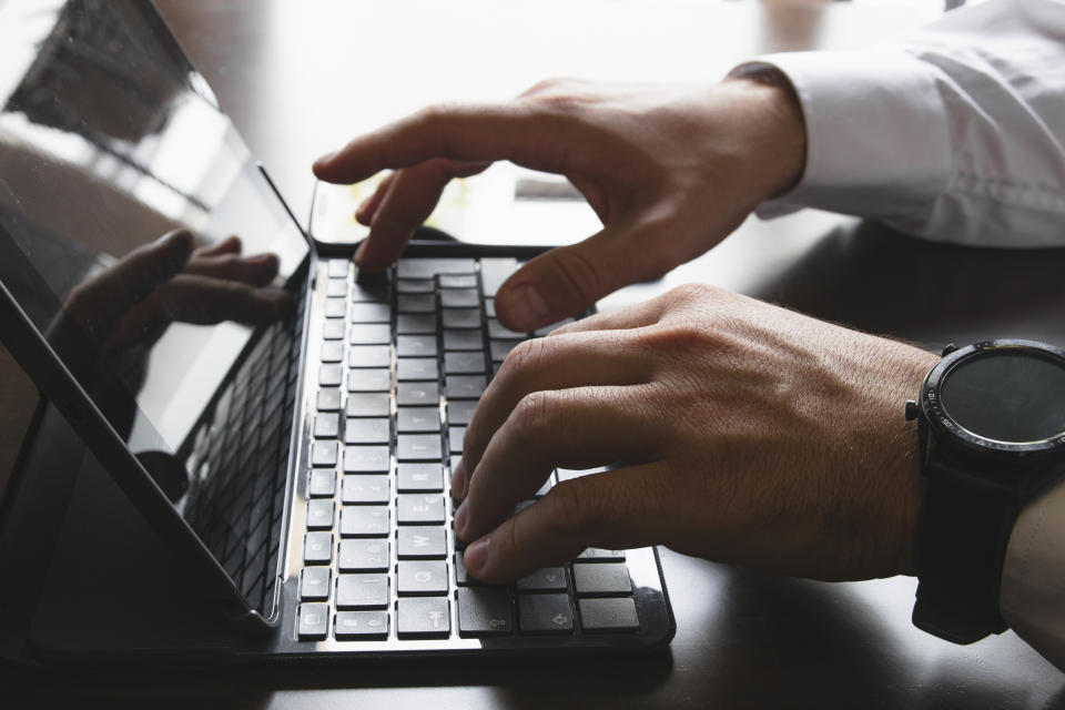 Close-up of the hands of a man in a shirt typing on the keyboard of a tablet or laptop. On her wrist she wears a smartwatch and a smarhphone in the background. Horizontal photography