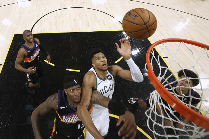 Milwaukee Bucks' Giannis Antetokounmpo (34) shoots over Phoenix Suns' Torrey Craig (12) during the second half of Game 1 of basketball's NBA Finals, Tuesday, July 6, 2021, in Phoenix. (Christian Petersen/Pool Photo via AP)