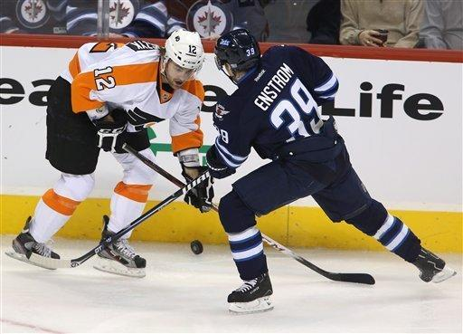 Philadelphia Flyers' Harry Zolnierczyk (12) and Winnipeg Jets' Tobias Enstrom (39) battle for control of the puck during the second period of an NHL hockey game in Winnipeg, Manitoba, Tuesday, Feb. 12, 2013. (AP Photo/The Canadian Press, Trevor Hagan)