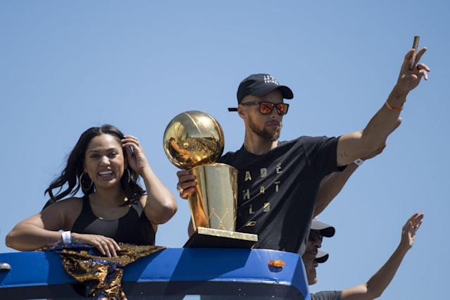 <p>Golden State Warriors guard Stephen Curry (30) waves to the crowd holding the championship trophy next to wife Ayesha Curry (left) during the Warriors 2017 championship victory parade in downtown Oakland. Mandatory Credit: Kyle Terada-USA TODAY Sports </p>