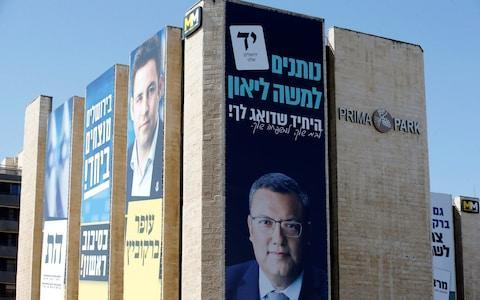 Moshe Lion (right poster) is facing Ofer Berkovtch (left poster) in Tuesday's election - Credit: REUTERS/Ronen Zvulun