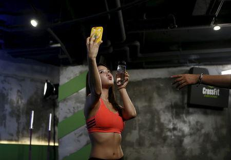 """Ray Yang, a celebrity trainer, takes a selfie before the start of a workout session during TV program """"The Body Show"""" at a gym in Seoul, September 19, 2015. REUTERS/Kim Hong-Ji"""
