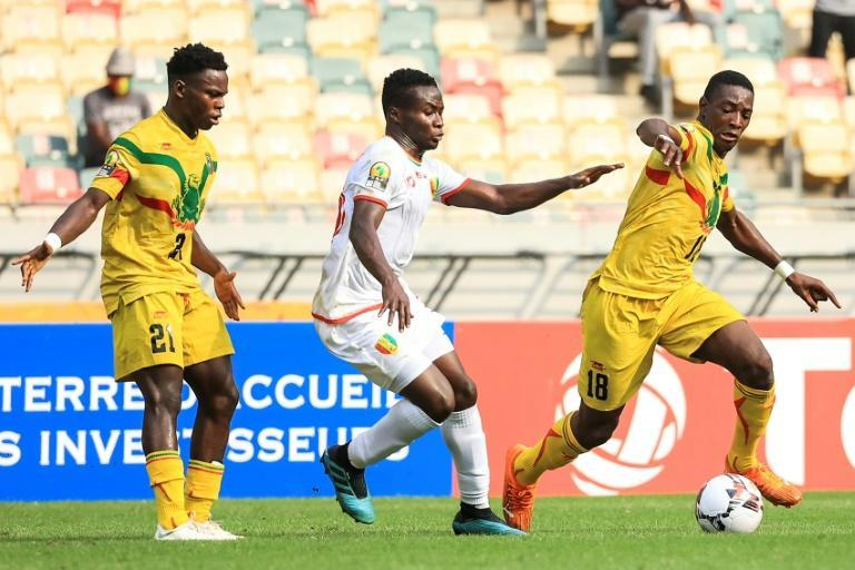 Morlaye Sylla (C) of Guinea is surrounded by Malians in an African Nations Championship semi-final in Douala, which Mali won on penalties after a 0-0 draw.