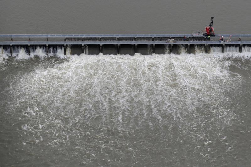 FILE- In this May 10, 2019 file photo, workers open bays of the Bonnet Carre Spillway, to divert rising water from the Mississippi River to Lake Pontchartrain, upriver from New Orleans, in Norco, La. Floodwaters carried down from the Midwest are killing oysters and driving crabs, shrimp and finfish out of Louisiana and Mississippi bays and marshes to saltier waters. (AP Photo/Gerald Herbert, File)
