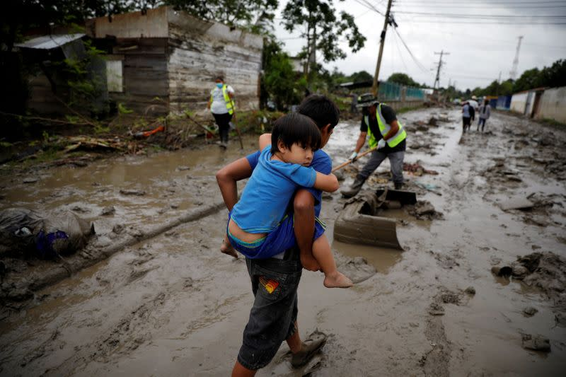 FILE PHOTO: A child carries his brother in a street covered in mud after the floods caused by the rains brought by Hurricanes Eta and Iota, in La Lima