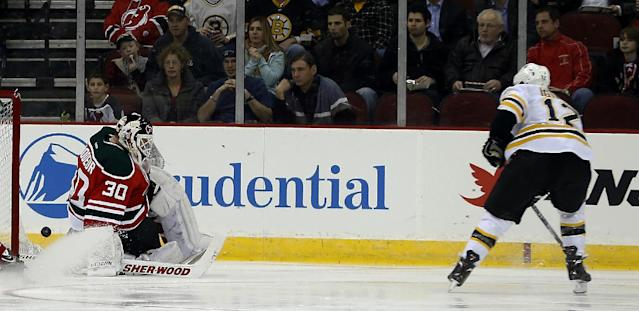 A shot by Boston Bruins right wing Jarome Iginla (12) gets pass New Jersey Devils goalie Martin Brodeur (30) for a goal during the second period of an NHL hockey game, Tuesday, March 18, 2014, in Newark, N.J. (AP Photo/Julio Cortez)