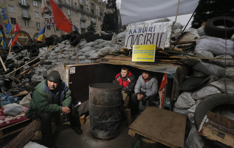 "Pro-European Union activists warm themselves sitting in their shelter inside a barricade during a rally in Independence Square, Kiev, Ukraine, Wednesday, Dec. 18, 2013. Russian President Vladimir Putin and Ukrainian President Viktor Yanukovych both pledged Tuesday, Dec. 17, 2013 to boost economic and trade ties to expand the ""strategic partnership"" between the two neighbors. (AP Photo/Dmitry Lovetsky)"
