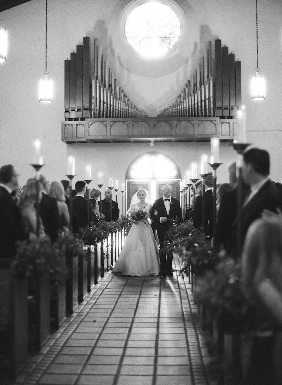 <p>Inside, the ceremony altar was framed by two large arrangements in tall urns, and every other pew was embellished with cascading foliage. Campbell was accompanied by her father as she made her way down the aisle—and saw John for the first time that day.</p>
