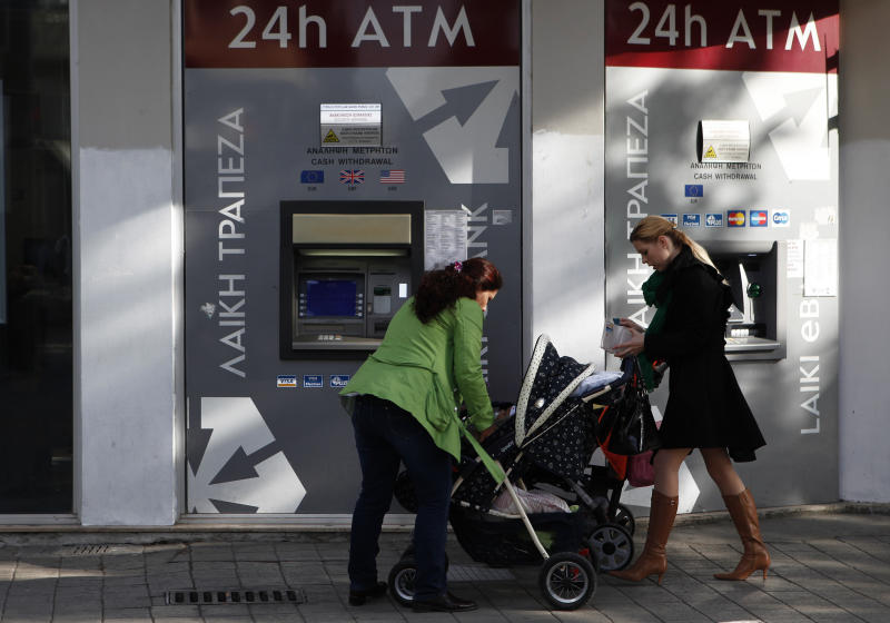 Women with their babies in baby strollers are seen outside of ATM machines at Elephterias (Liberty) square at the old city of capital Nicosia, Cyprus, Tuesday, Jan. 22, 2013. Cyprus says it has no reason to consider privatizing state-owned companies now because it's not yet certain that its public debt burden would be too heavy to bear once it receives rescue money from international creditors. (AP Photo/Petros Karadjias)