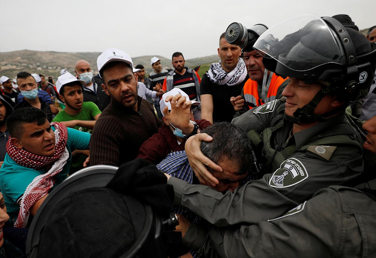 <p>An Israeli border policeman tries to detain a Palestinian protester during clashes at a protest marking Land Day in the West Bank village of Madama, near Nablus, March 30, 2017. (Mohamad Torokman/Reuters) </p>
