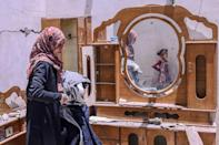 A Palestinian woman searches for her famiy's belongings at their house after it was destroyed by an Israeli air strike, in the city of Rafah, in the southern Gaza Strip on May 16