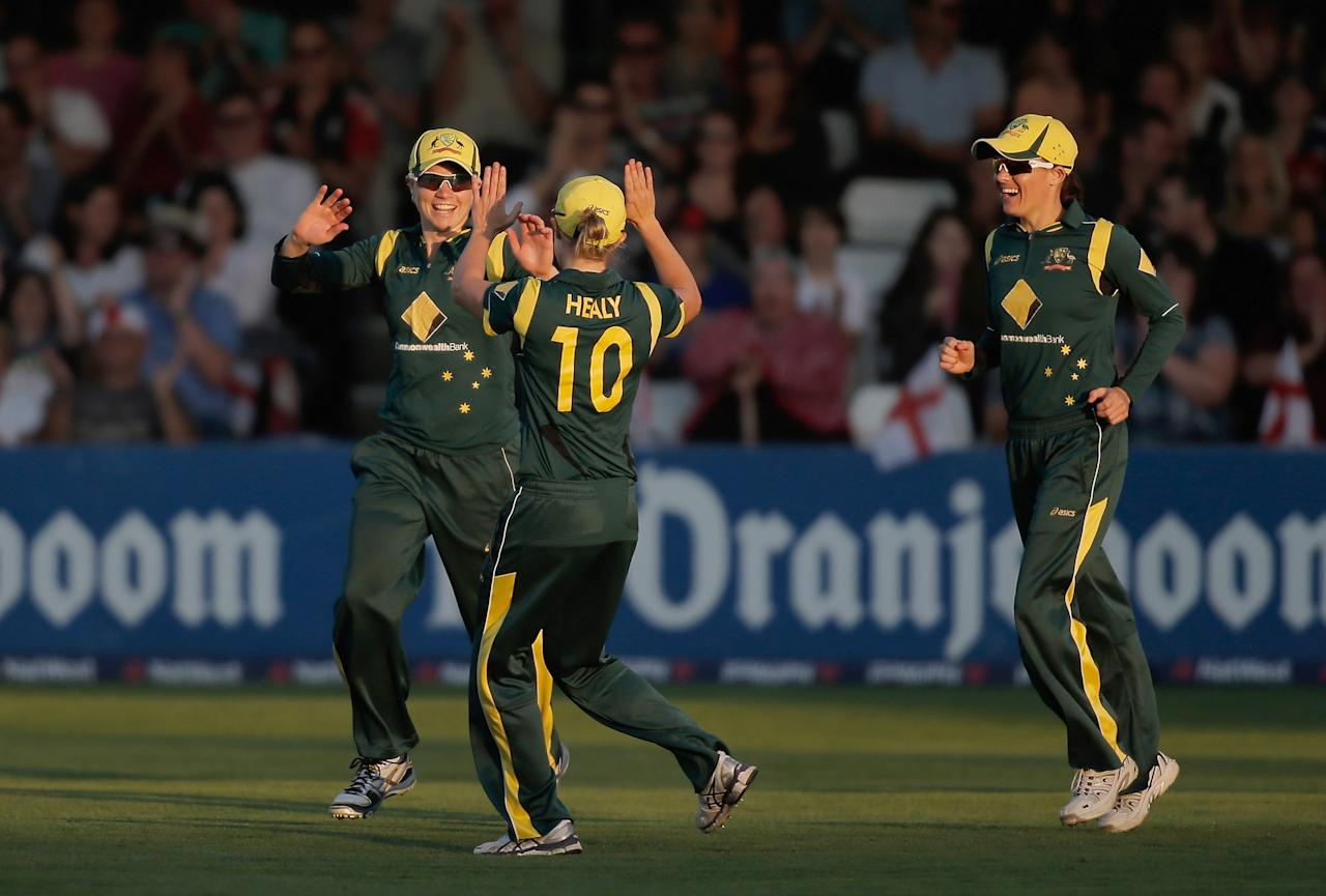 CHELMSFORD, ENGLAND - AUGUST 27: Jess Cameron of Australia (L) is congratulated by team-mates after taking a catch to dismiss Heather Knight of England (not pictured) during the first NatWest T20 match between England and Australia at the Ford County Ground on August 27, 2013 in Chelmsford, England.  (Photo by Harry Engels/Getty Images)