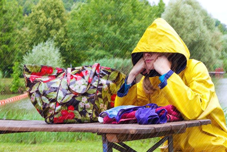 Image of a woman sitting in the rain.