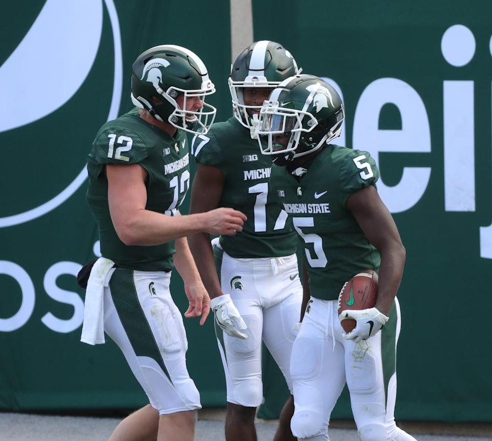 Michigan State quarterback Rocky Lombardi (12) and receiver Tre Mosley (17) congratulate receiver Jayden Reed after his touchdown during MSU's 38-27 loss on Saturday, Oct. 24, 2020, at Spartan Stadium.