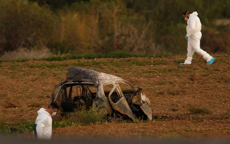 Forensic experts examine the scene of the car bombing that killed Daphne Caruana Galizia