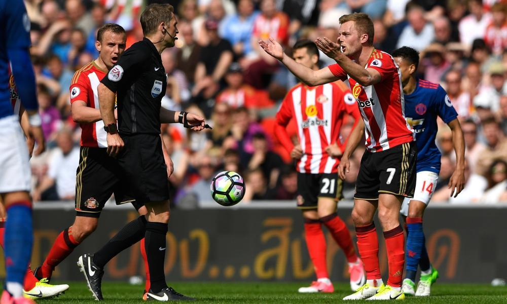 Sebastian Larsson attempts to plead his case as the referee Craig Pawson reaches for his red card after a foul by the Sunderland man on Manchester United's Ander Herrera.