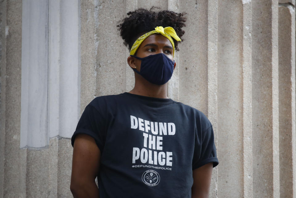 A protester stands on the steps of a government building near an encampment outside City Hall, Tuesday, June 30, 2020, in New York. City Council members were due to debate and vote Tuesday night on a plan to shift $1 billion from policing to education and social services, with time running short ahead of the fiscal year that begins Wednesday. (AP Photo/John Minchillo)