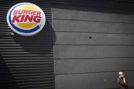 A man talks on his phone underneath a Burger King logo outside the restaurant in the Brooklyn borough of New York