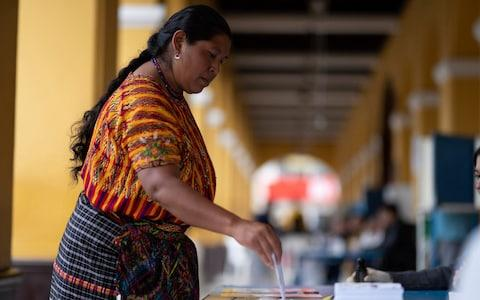 A woman casts her vote at a polling station, in San Juan Sacatepequez, - Credit: Santiago Billy/AP