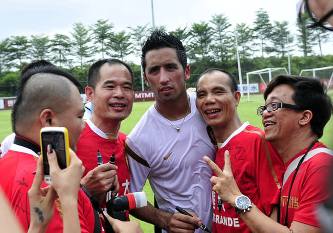 Paraguayan football player Lucas Barrios (C) poses with his Chinese fans during his first training session with his new team the Guangzhou Evergrande under World Cup-winning coach Marcello Lippi, in Guangzhou, south China's Guangdong province on June 18, 2012.  Guangzhou will take on Saudi Arabia's Al Ittihad in the AFC Champions league two-leg quarterfinals on September 19 and October 2.      CHINA OUT       AFP PHOTOSTR/AFP/GettyImages