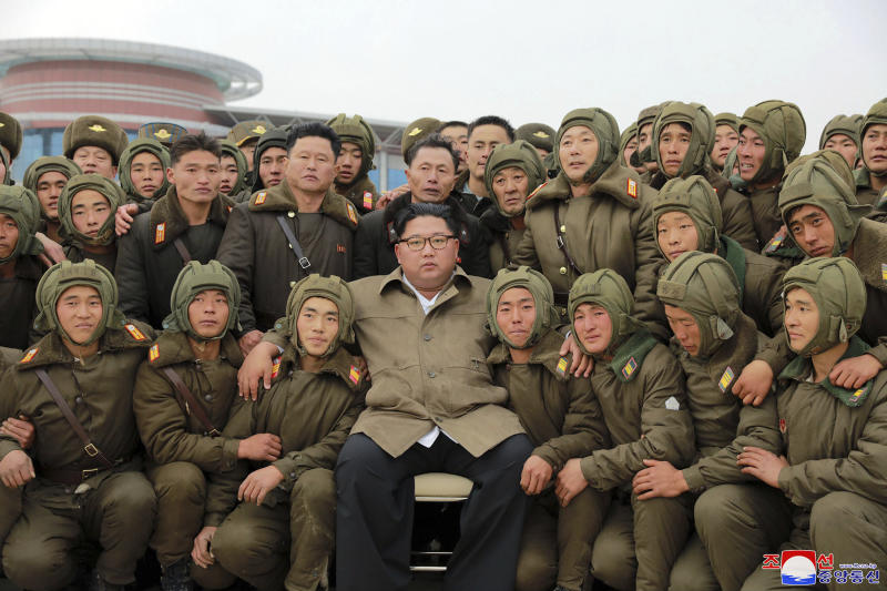 """In this undated photo provided on Monday, Nov. 18, 2019, by the North Korean government, North Korean leader Kim Jong Un, center, poses with North Korean air force sharpshooters and soldiers for a photo at an unknown location in North Korea. Kim supervised a parachuting drill of military sharpshooters and vowed to build an """"invincible army,"""" displaying more defiance even as the United States and South Korea called off their own exercises to create space for nuclear diplomacy. Independent journalists were not given access to cover the event depicted in this image distributed by the North Korean government. The content of this image is as provided and cannot be independently verified. Korean language watermark on image as provided by source reads: """"KCNA"""" which is the abbreviation for Korean Central News Agency. (Korean Central News Agency/Korea News Service via AP)"""