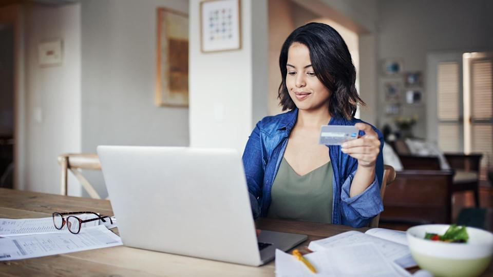 Shot of a young woman using a laptop and credit card while working from home.