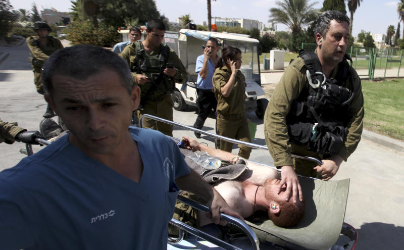 An injured Israeli soldier is wheeled into Soroka hospital in the southern town of Beersheva, Israel, Friday, Sept  21, 2012, following an exchange of fire with militants along Israel's southern border with Egypt. Military spokeswoman Lt. Col. Avital Leibovich says the militants were armed with weapons and were wearing explosive belts and flak jackets. She said they opened fire on Friday on Israeli troops guarding a team of workers building a border fence between Israel and Egypt's Sinai desert. The Israeli troops returned fire, killing the militants.(AP Photo/Yehuda Lahiyani) ISRAEL OUT