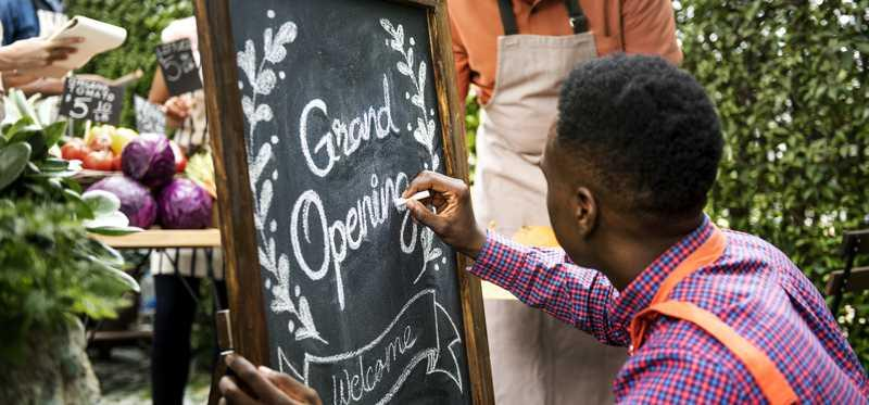 Man writing grand opening on a chalkboard sign.