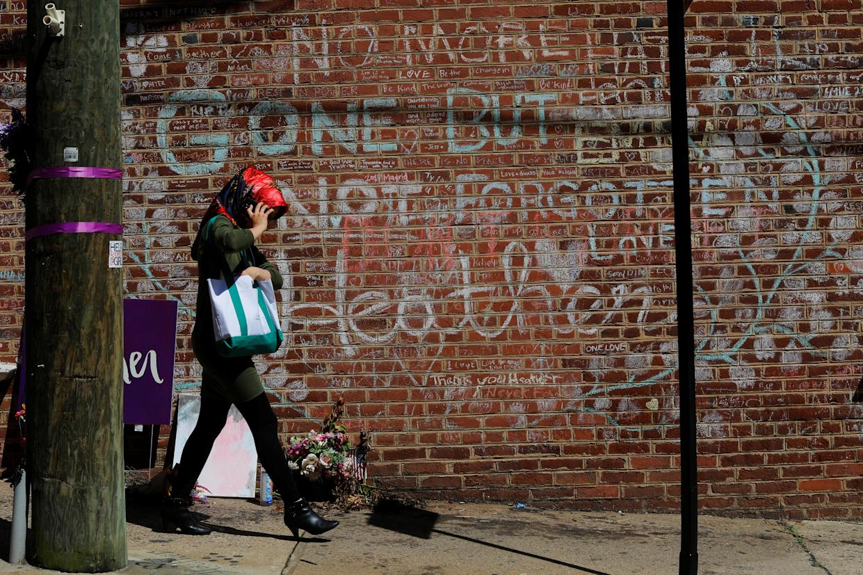 A woman walks past tributes written at the site where Heather Heyer was killed during the 2017 white nationalist rally in Charlottesville, Va,, on Aug. 1, 2018. (Photo: Brian Snyder/Reuters)