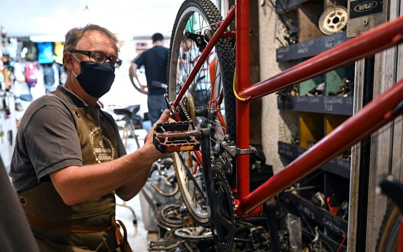 An employee works in a bicycle repair shop in Lille, northern France. r shop on September 14, 2020, in Lille, northern France. The French government will commit an additional 20 million euros in subsidies for bike repairs - AFP