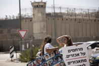 """Members of the group Choosing Life, that includes relatives of Israelis killed in Palestinian attacks, protest outside of Ofer Prison near Jerusalem, Thursday, Sept. 9, 2021, after the escape of six Palestinian prisoners from Gilboa prison on Monday. At left is a poster depicting slain Israelis; at right is a poster that reads: """"compassion for the cruel is cruel to the murdered."""" (AP Photo/Maya Alleruzzo)"""