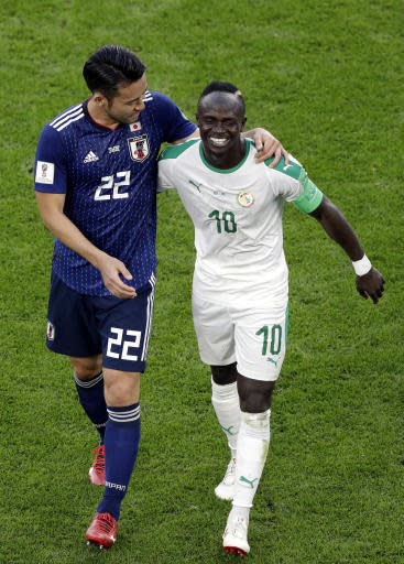 Japan's Maya Yoshida, left, shares a light moment with Senegal's Sadio Mane during the group H match between Japan and Senegal at the 2018 soccer World Cup at the Yekaterinburg Arena in Yekaterinburg , Russia, Sunday, June 24, 2018. (AP Photo/Mark Baker )