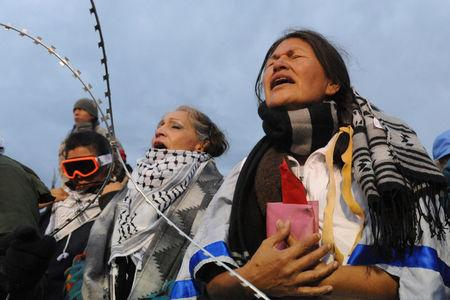 Women hold a prayer ceremony on Backwater Bridge during a protest against plans to pass the Dakota Access pipeline near the Standing Rock Indian Reservation, near Cannon Ball, North Dakota, U.S. November 27, 2016. REUTERS/Stephanie Keith