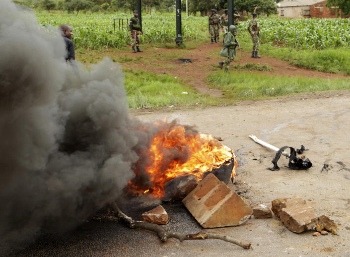 Soldiers patrol near a barricade A soldier patrols as protestors gather during a demonstration over the hike in fuel prices in Harare, Zimbabwe, Tuesday, Jan. 15, 2019. A Zimbabwean military helicopter on Tuesday fired tear gas at demonstrators blocking a road and burning tires in the capital on a second day of deadly protests after the government more than doubled the price of fuel in the economically shattered country. (AP Photo/Tsvangirayi Mukwazhi)
