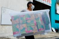 A mover collects a box of biscuits after police search a warehouse of Student Politicism, in Hong Kong