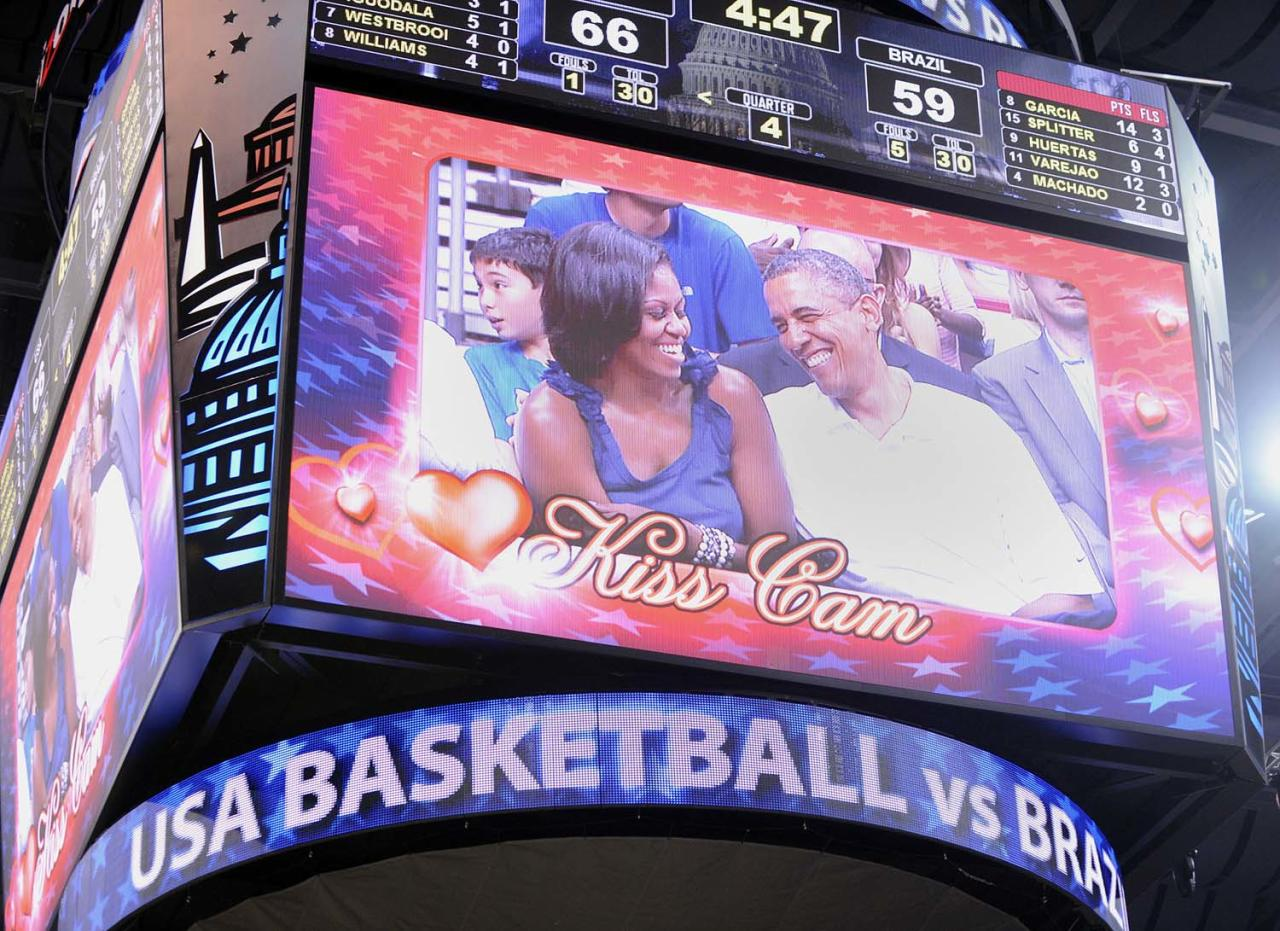 WASHINGTON, DC - JULY 16:  U.S. President Barack Obama laughs with first lady Michelle Obama as they appear on the 'Kiss Cam' as the US Senior Men's National Team and Brazil play during a pre-Olympic exhibition basketball game at the Verizon Center on July 16, 2012 in Washington, DC. (Photo by Leslie E. Kossoff-Pool/Getty Images)