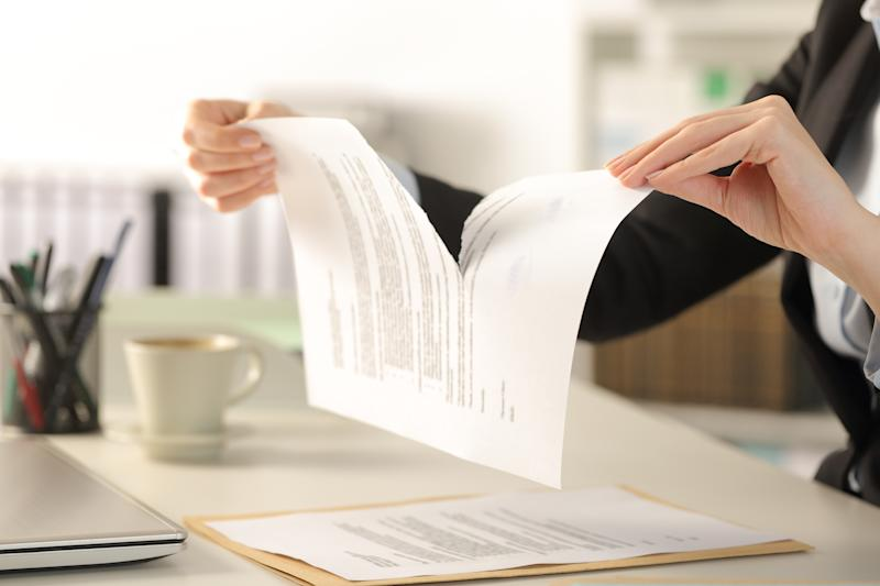 Close up of business woman hands breaking contract document sitting on a desk at the office.