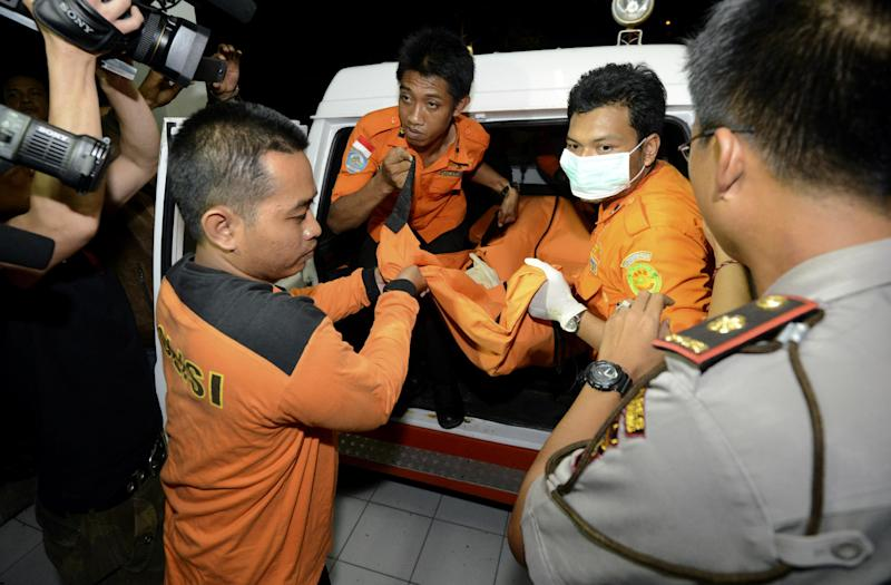 Indonesian rescue team members carry the body that a national rescue team said was of a Japanese diver, to morgue in Bali, Indonesia, Tuesday, Feb. 18, 2014. Seven Japanese scuba divers who had been missing off Indonesia's resort island of Bali since last week. Five were found alive Monday, police said. (AP Photo/Firdia Lisnawati)