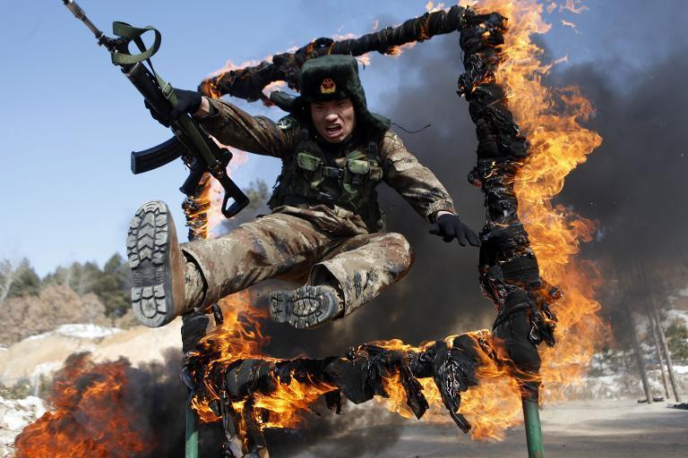 A soldier jumps through a ring of fire during a tactical training mission in Heihe, northeast China's Heilongjiang province, March 5, 2014